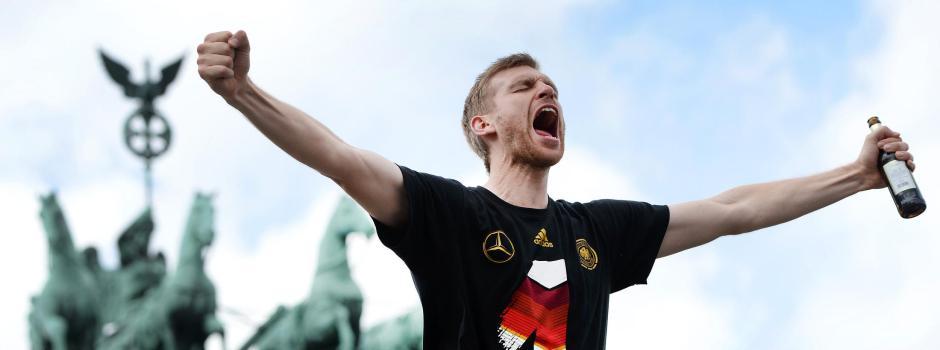 Der deutsche Nationalspieler Per Mertesacker jubelt am 15.07.2014 beim Empfang an der Fanmeile am Brandenburger Tor in Berlin. Nach 1954, 1974 und 1990 ist Deutschland mit einem Sieg über Argentinien zum vierten Mal Weltmeister geworden. Foto: Daniel Naupold/dpa +++(c) dpa - Bildfunk+++