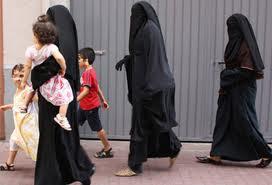 Tres catalanas pasean por una calle de Vilanova acompañadas de sus hijos.